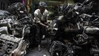 A man works on used car parts in Calcutta, India - 1 February 2011