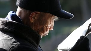 File photograph of an elderly man reading a newspaper on a street in Beijing, China