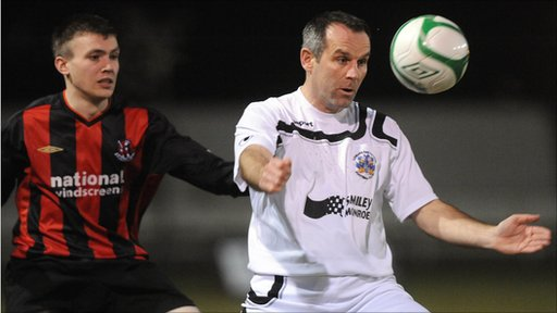 Stuart Dallas of Crusaders watches as Lisburn Distillery's Glenn Ferguson controls the ball