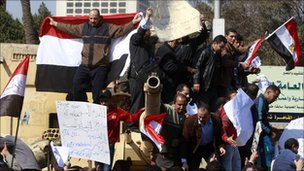 Pro-government supporters shout slogans on top of a tank near Tahrir Square, Cairo, 2 February 2011