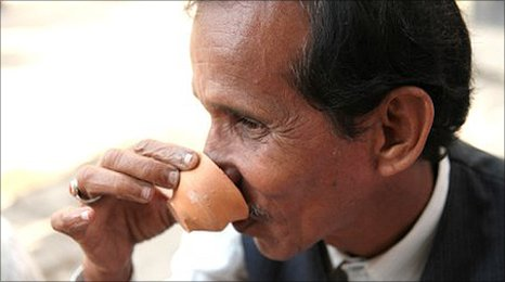 A Indian man drinking Chai in a clay cup