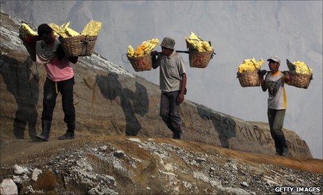 Heavily-laden miners walk back up out of the crater