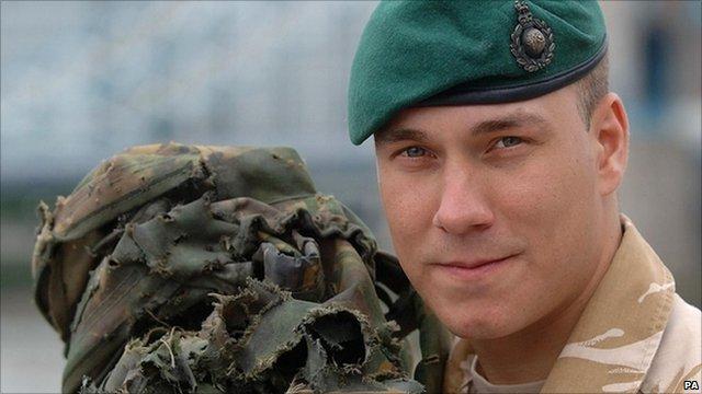 Lance Corporal Matthew Croucher holding a worn backpack