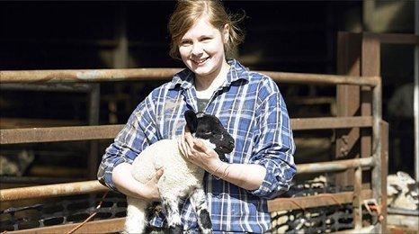girl carrying a lamb