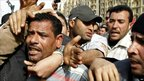 Egyptian anti-government protesters in Tahrir Square with a man they say is a supporter of President Hosni Mubarak - 4 February 2011