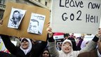 Women hold up anti-Mubarak posters at a protest in Alexandria, Egypt - 4 February 2011