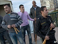 Egyptian police officer stands guard by a neighbourhood watch group