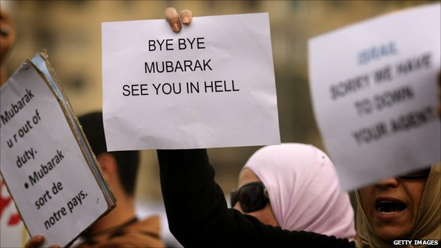 Egyptians shout slogans and hold up signs in Cairo on February 1, 2011