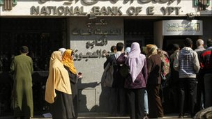 Egyptians wait at an automatic cash dispenser in Cairo