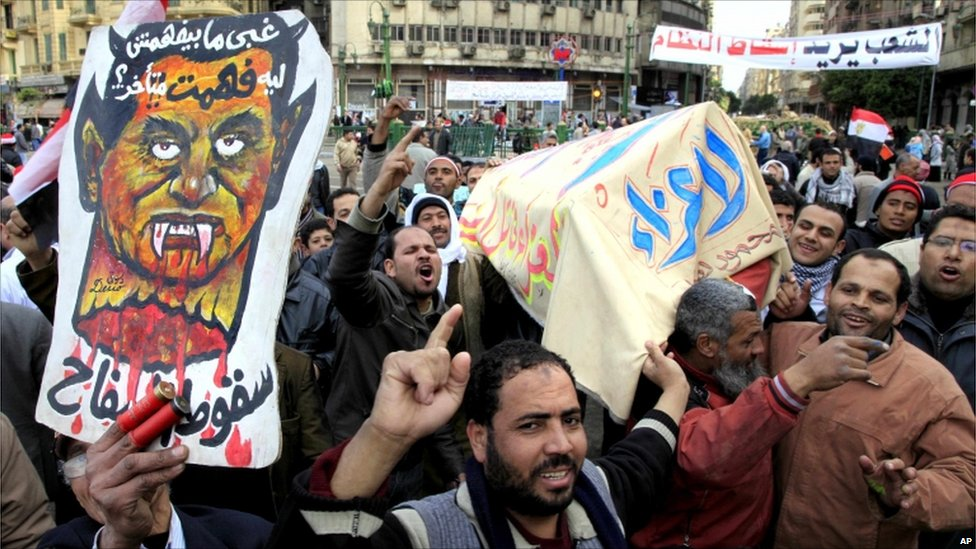 Egyptian anti-Mubarak protesters celebrate during a symbolic funeral for President Hosni Mubarak.