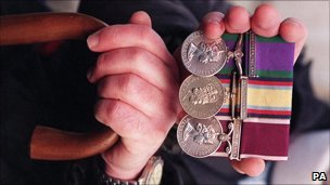 An armed forces veteran holds his medals