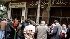 People stand in the line to make withdrawals outside Al Ahli United Bank in Cairo