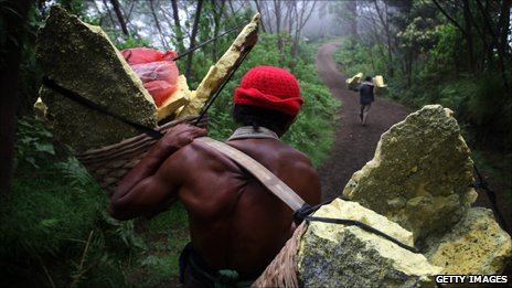 Miner carrying heavily laden baskets