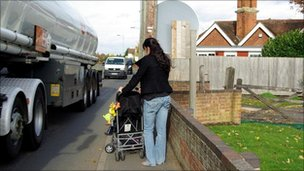 Woman pushing a pushchair on the pavement as a lorry goes past