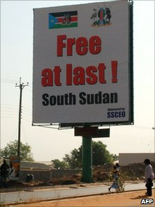 Southern Sudanese walk under a billboard in Juba on 7 February 2011, which celebrates the choice of the south to separate from the north