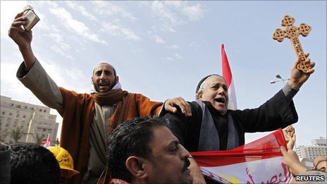 A Muslim holding a Koran (L) and a Coptic Christian holding a cross in Cairo's Tahrir Square - 6 February 2011