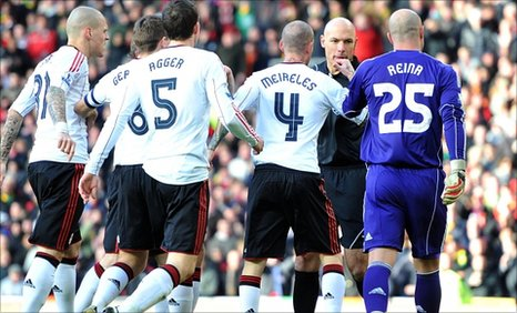 Liverpool players confront referee Howard Webb