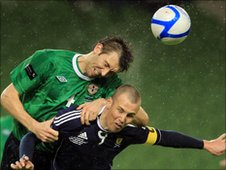 Gareth McAuley rises above Scotland's Kenny Miller to head clear