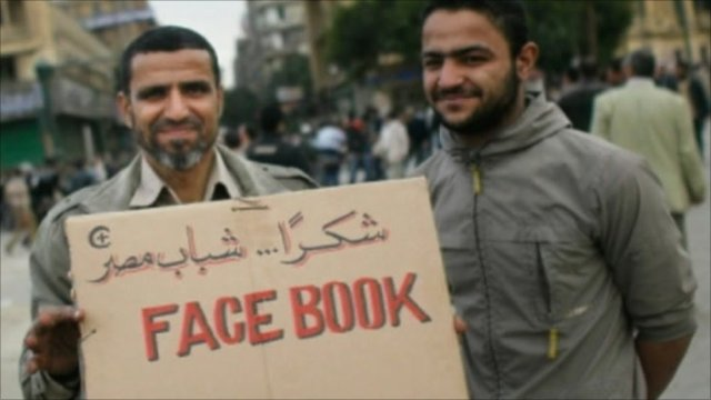 Egyptian protesters with Facebook sign