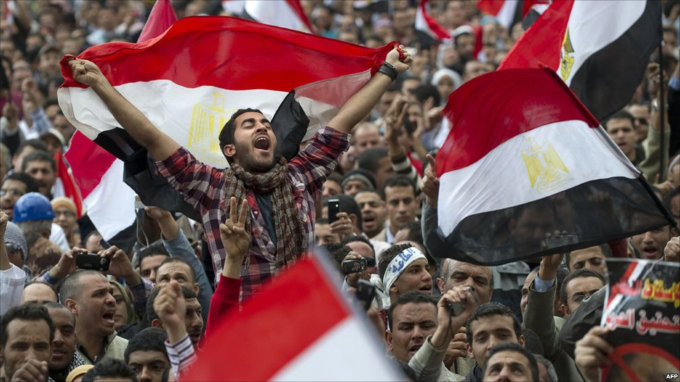 Egyptian anti-government demonstrators wave Egyptian flags at Cairo's Tahrir Square