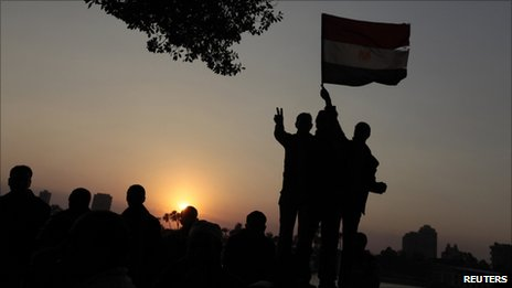 The sun sets on protesters as they demonstrate in Tahrir Square in Cairo February 11, 2011. A