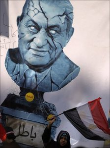 "An Egyptian girl waves a national flag beneath a picture of a cracked bust of Egypt's President Hosni Mubarak with Arabic writing below reading ""invalid"", Cairo, Egypt, 11 February 2011"
