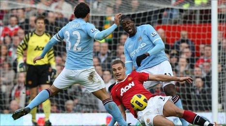 Nemanja Vidic, Manchester United, tackles Carlos Tevez, Mancheter City