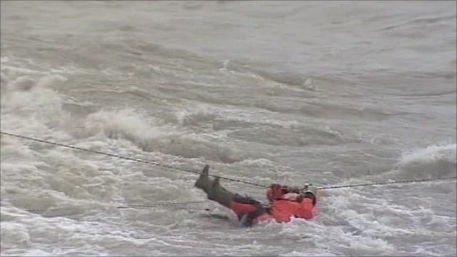 Man clinging on to rescue rope