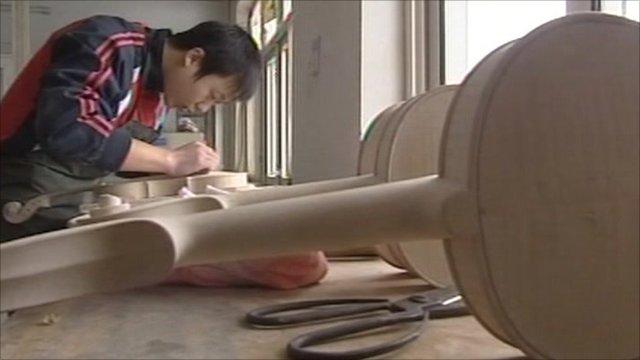 Migrant worker making violin