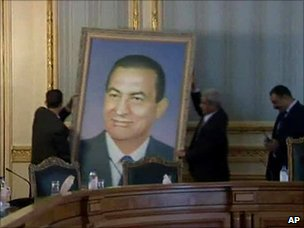 Officials remove a portrait of Hosni Mubarak at the cabinet building in Cairo, 13 February