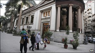 An Egyptian family walks past the closed Egyptian stock exchange building