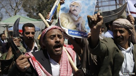 Government loyalists armed with daggers brandish a poster of Yemeni President Ali Abdullah Saleh in the capital Sanaa, 14 February