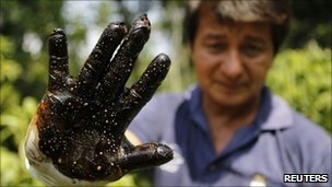 Environmentalist Donald Moncayo shows his glove after conducting a test made on an affected field in Lago Agrio, 25/01
