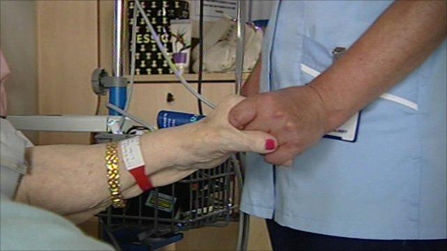 A nurse holds an elderly patient's hand
