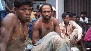 Rohingya men wait for medical treatment after being rescued, at a port in Aceh province, Indonesia