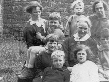 Syd Bailey (being held by a woman) with his cousin (white dress) and inmates at Morda workhouse in the 1920s