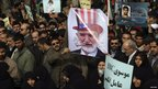 Mourners at the funeral of student Sanee Zhaleh, with poster portraying opposition leader Mehdi Karroubi as Uncle Sam - photo 16 February