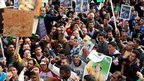 Libyan pro-government supporters hold portraits of leader Muammar Gaddafi during a gathering in Tripoli on 16 February