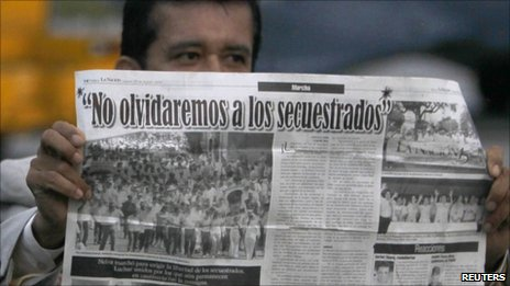 "Politician Armando Acuna holds a newspaper with an article headlined, ""We will not forget the kidnapped"" upon his arrival at Catam airport in Bogota February 11, 2011"