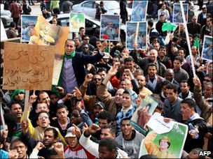 Libyan pro-government supporters hold portraits of leader Moamer Kadhafi