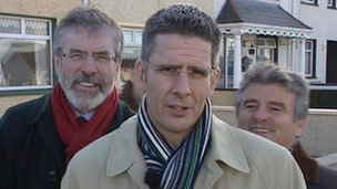 The BBC's Mark Simpson and Sinn Fein President Gerry Adams behind him (17 Feb 2011)