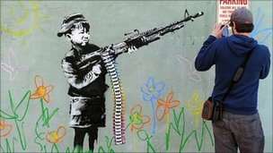 A Banksy work of a child wielding a machine gun pointing at a no parking sign.