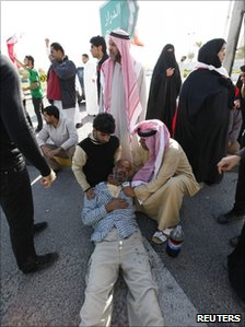 A protester, who collapsed after inhaling tear gas, lies on the ground, 14 February 2011