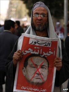 A member of the Muslim Brotherhood organisation hold the cover of a local paper depicting former Egyptian President Hosni Mubarak, 2011