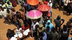 Ugandan voters wait in line at a polling station in the capital Kampala on February 18, 201