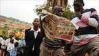 People read a newspaper while waiting in line at a polling station in Uganda's capital Kampala on 18 February 2011
