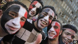 Young Egyptians wearing facepaint in the colors of the national flag arrive at Tahrir square to celebrate the fall of the regime of former President Hosni Mubarak one week ago, 18 February 2011