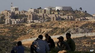 Palestinian teenagers sit opposite the Jewish settlement of Modiin in the West bank, 18 February