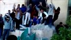 A frame from amateur video footage reportedly showing Libyan protesters knocking down a monument to Colonel Muammar Gaddafi's 'Green Book' in the city of Tobruk, Libya, 17 February 2011