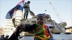 A boy sits atop an army tank during a victory celebration in Tahrir Square, Cairo, 18 February 2011